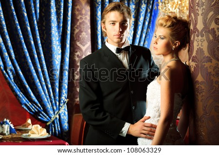 Charming bride and groom on their wedding celebration in a luxurious restaurant.