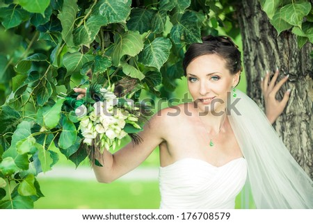 Charming bride walks in the park. Soft focus. - stock photo