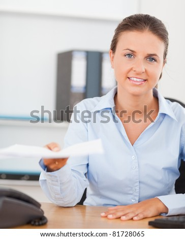 Charming brunette businesswoman handing out a paper in her office