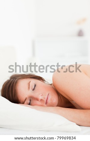 Charming brunette female having a rest while lying on a bed