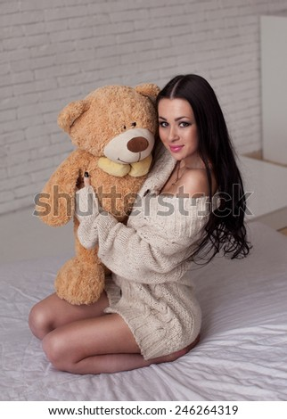 Charming brunette in bed with her teddy bear  - stock photo