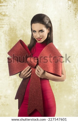 charming brunette lady wearing red sexy dress,  taking big christmas bow in the hand and smiling  - stock photo
