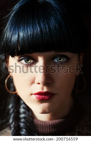Charming brunette paranormal look, shadow of light and dark on a face. - stock photo
