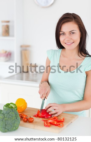 Charming brunette slicing a pepper in her kitchen