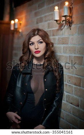 Charming brunette with black leather jacket against red bricks wall. Sexy gorgeous young woman with long curly hair. Portrait of sensual woman with red lips and provocative low-cut neck  - stock photo