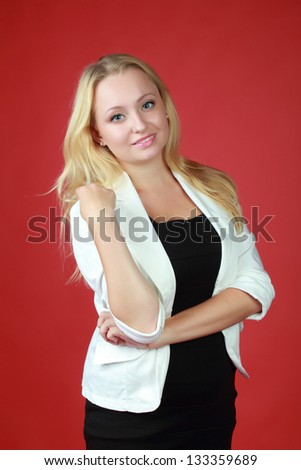 Charming business woman with long hair and a sweet smile on red background - stock photo