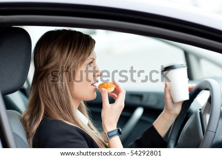 Charming businesswoman eating and holding a drinking cup while driving to work - stock photo