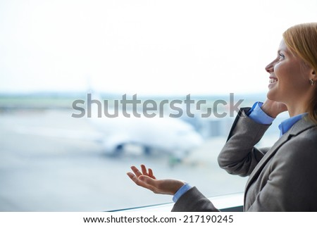 Charming businesswoman speaking on cellular phone in airport - stock photo