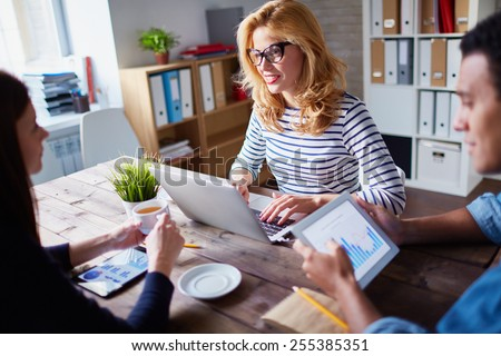 Charming businesswoman typing and talking to her colleagues at meeting