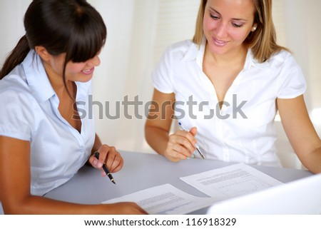 Charming businesswomen reading documents at workplace
