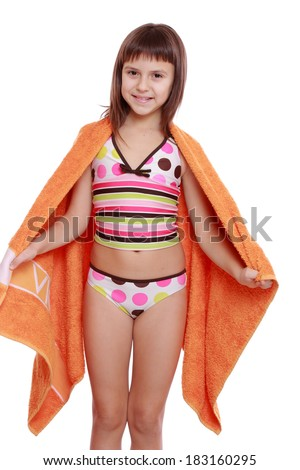 Charming caucasian little girl in swimsuit holding orange towel isolated over white background/Young girl holding orange towel - stock photo