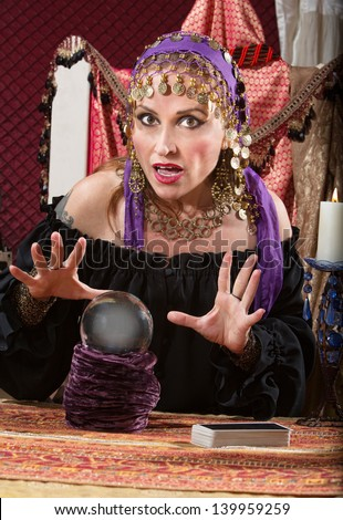 Charming Caucasian woman in headscarf waving hands over crystal ball - stock photo