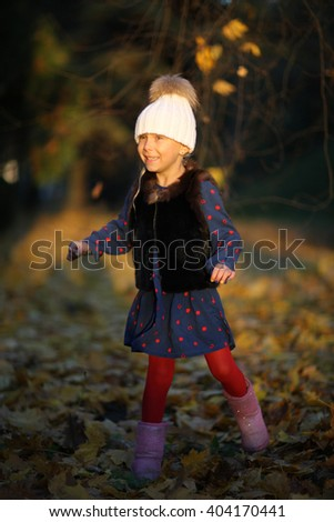 Charming cheerful girl dancing outdoors in autumn - stock photo