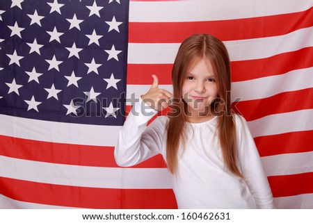 Charming cheerful little girl holding her thumb up on the background of the American flag