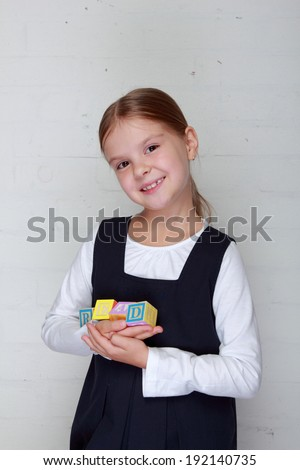 """Charming cheerful little girl in school uniform holding the word """"read"""" from the children's blocks/Child playing with letter cubes - stock photo"""