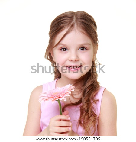Charming cheerful little girl with a beautiful smile in a bright pink dress holding a gerbera on a white background