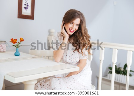 Charming cheerful young woman with curly long hair sitting in cafe and smiling - stock photo