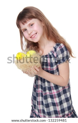 Charming child holds Easter basket with eggs on white background on Holiday