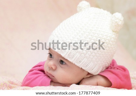 Charming child. Little girl in white knitted bear hat