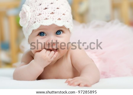 Charming child. Little girl with hat lying on her stomach and sucks fingers - stock photo