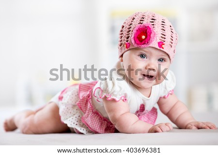 Charming child little girl with hat lying on her stomach on bed - stock photo