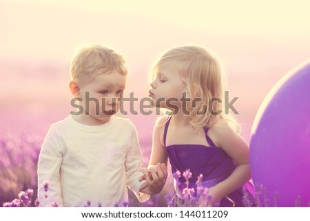 Charming children on lavender field at sunset, little girl kissing a boy - stock photo