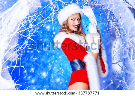 Charming Christmas girl with a beautiful smile standing in a magic snowy forest. Christmas time.