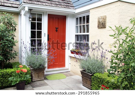 Charming colorful front door entrance with blooming lavender in containers.  - stock photo