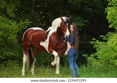 Charming cowgirl with dark horses walking in the woods