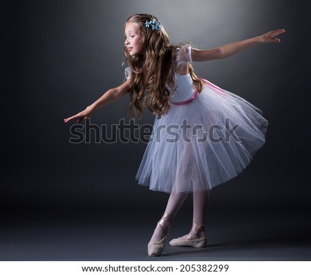 Charming curly girl dancing ballet in studio - stock photo