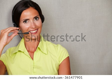 Charming customer service operator with headset and wearing casual clothing while smiling and looking at camera on grey texture background - stock photo
