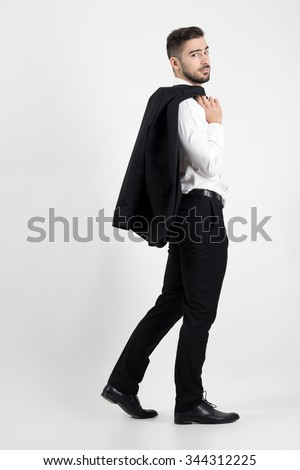 Charming elegant man walking carrying suit jacket over his shoulder. Side view.  Full body length portrait over gray studio background. - stock photo