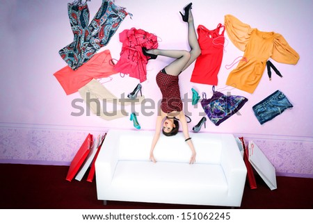 Charming fashionable woman flying in the room, surrounded by lots of her clothes. - stock photo