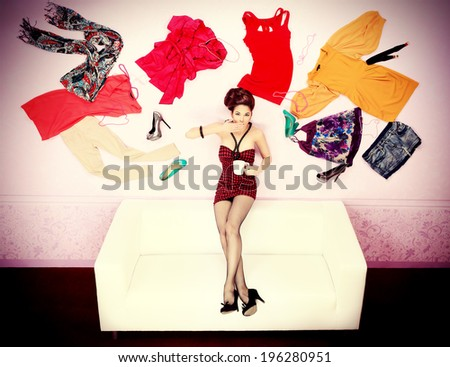 Charming fashionable woman flying in the room, surrounded by lots of her clothes.