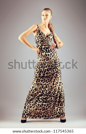 Charming fashionable young woman posing over gray background.