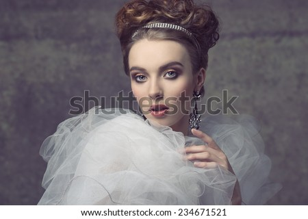 charming female baroque retro dame posing in creative fashion portrait with elegant hair-style, precious tiara and earrings, vintage romantic dress with frill veil collar and stylish make-up.  - stock photo