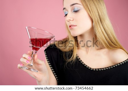 Charming female drinks cocktail against pink background - stock photo