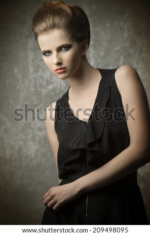 charming female posing in fashion portrait with elegant creative hair-style, stylish make-up and black dress  - stock photo