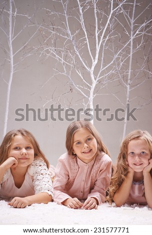 Charming friends with long blond hair looking at camera in winter forest - stock photo