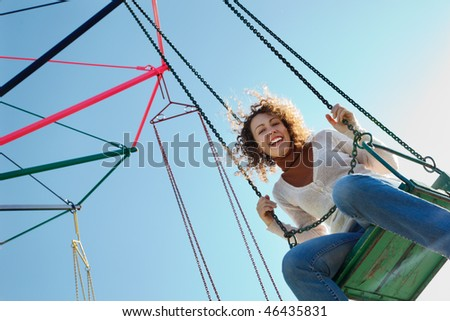 Charming girl goes for drive on roundabout. Looking into camera. - stock photo