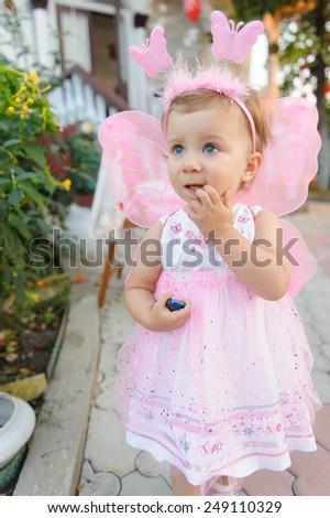 charming girl in fairy dress biting her finger - stock photo