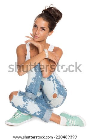 Charming girl in stylish ripped jeans sitting on the floor.  - stock photo