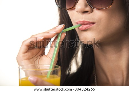 Charming girl is drinking orange juice. Pretty lady with the glass close up.  - stock photo