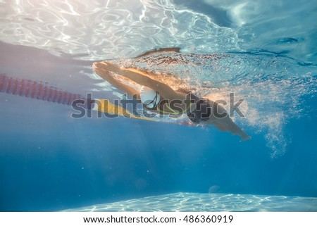 Charming girl swims in back crawl style underwater in the swimming pool outdoors. She wears a black-lime swimsuit, a white swim cap and swim glasses. Sunlight falls from above. Horizontal.