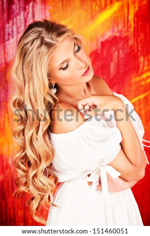 Charming girl with beautiful blonde hair over vivid background. - stock photo