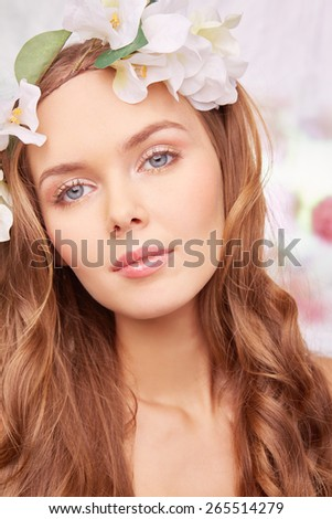 Charming girl with curly hair looking at camera - stock photo