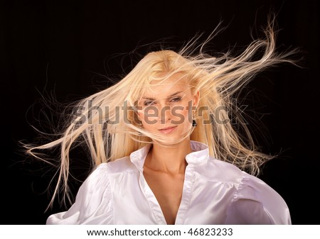 Charming girl with hair fluttering on wind, it is isolated on black background.