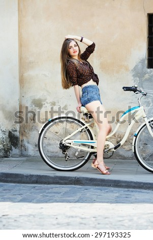 Charming girl with long hair wearing on dark blouse and blue shorts is posing on the bicycle on the old wall background, on the street of European city - stock photo