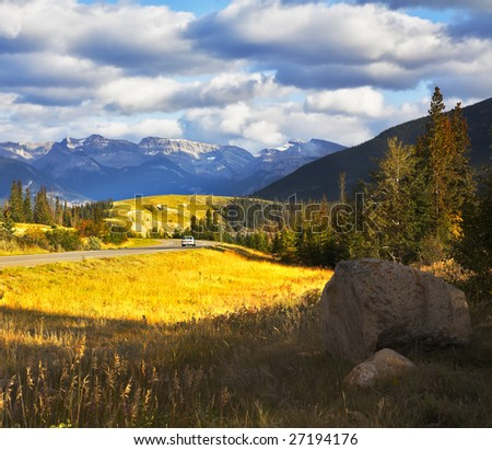 Charming glade with a yellow autumn grass and road beside in national park Jasper in Canada - stock photo
