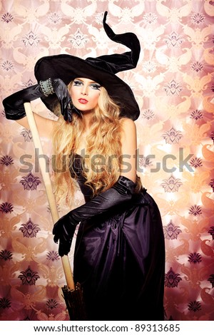 Charming halloween witch over vintage background. - stock photo